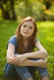 Schönes red-haired Mädchen, das auf Gras sitzt Lizenzfreies Stockfoto