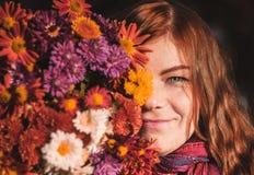 Schönes redhaired Mädchen mit Blumen stockfotos