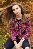 Schönes reizend junges attraktives Mädchen mit großen blauen Augen, mit dem langen dunklen Haar im Herbstwald sitzt auf einem Bau Stockfotografie