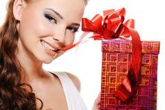 Schönes reizvolles Frauengesicht mit einem Weihnachtsgeschenk Lizenzfreies Stockbild