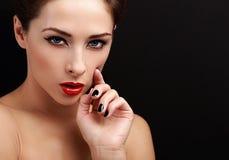 Schönes reizvolles Frauenportrait Schwarzer Eyeliner, roter Lippenstift und schwarzer Nagellack Lizenzfreies Stockbild