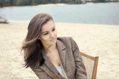 Schönes reizvolles Mädchen, das im Stuhl auf dem Strand sitzt Lizenzfreie Stockfotos