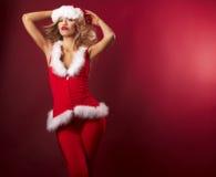 Schönes reizvolles Mädchen, das Weihnachtsmann-Kleidung trägt Stockfotografie