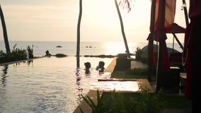 Schönes Restaurant auf dem Strand Ein romantischer Platz für Liebhaber Ein Mann und ein Mädchen schwimmen im Pool Sonnenuntergang stock video footage
