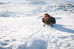 Schönes Rodeln der jungen Frau glücklich im Schnee Stockbild