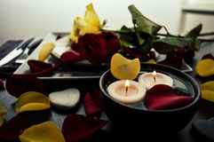 Schönes romantisches Abendessen mit den Blumenblumenblättern, Rosen, Kerzen Valentinstagliebes-Nachtdatum lizenzfreie stockfotos