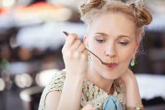 Schönes romantisches blondes Mädchen im Retrostil essend von einem spoo Lizenzfreie Stockfotografie