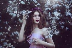 Schönes romantisches Mädchen mit dem langen Haar im rosa Kleid nahe blühendem Baum Stockfotografie