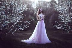 Schönes romantisches Mädchen mit dem langen Haar im rosa Kleid nahe blühendem Baum Lizenzfreie Stockfotografie