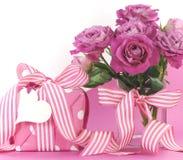 Schönes rosa Geschenk und Rosen auf rosa und weißem Hintergrund mit Kopienraum Stockfoto