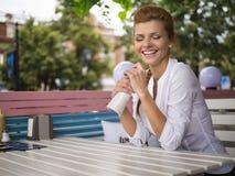 Schönes rotes Haarfrauenlachen über Freiencafé lizenzfreie stockfotos