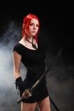 Schönes rotes Haarmädchen mit katana Klinge Lizenzfreies Stockfoto