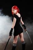 Schönes rotes Haarmädchen mit katana Klinge Stockfotografie