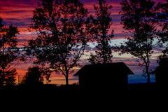 Schönes rotes Sonnenunterganghaus und das Baumschattenbild Lizenzfreies Stockbild