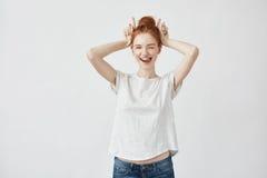 Schönes Rothaarigemädchen, welches das Lächeln blinzelt, Hasehände zeigend Lizenzfreie Stockfotos