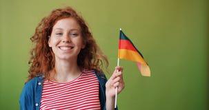 Schönes Rothaarigemädchen, welches die deutsche Flagge lächelt auf grünem Hintergrund hält stock footage