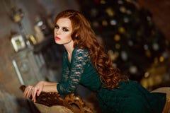 Schönes rothaariges gelocktes Mädchen in einem grünen Kleid gegen das BAC Stockbilder