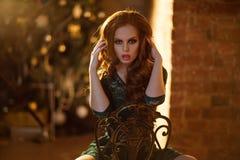 Schönes rothaariges gelocktes Mädchen in einem grünen Kleid gegen das wal Stockfotografie
