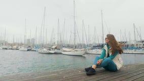 Schönes rothaariges Mädchen, das auf dem Pier sitzt Gegen die Yacht und das Meer Schiffsparken stock footage