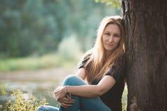 Schönes rothaariges Mädchen, das gegen einen Baum nahe Fluss am Wald sitzt Stockbilder