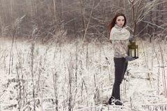 Schönes rothaariges Mädchen in den Handschuhen gehend mit einer Lampe in einem fabelhaften Winterwald Lizenzfreie Stockfotografie