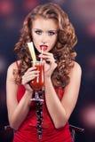 Schönes rothaariges Mädchen in einem roten Cocktailkleid Stockfotos