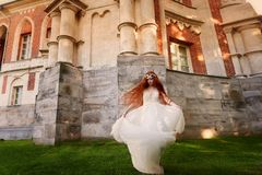Schönes rothaariges Mädchen mit dem langen gelockten Haar in der Braut, in einem langen Spitzekleid Eine Naturschönheit Stockfotografie