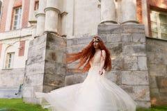Schönes rothaariges Mädchen mit dem langen gelockten Haar in der Braut, in einem langen Spitzekleid Eine Naturschönheit Lizenzfreies Stockbild