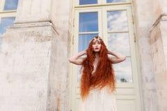 Schönes rothaariges Mädchen mit dem langen gelockten Haar in der Braut, in einem langen Spitzekleid Eine Naturschönheit Lizenzfreies Stockfoto