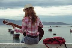 Schönes rothaariges Mädchen mit einer Gitarre Lizenzfreie Stockfotografie