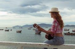 Schönes rothaariges Mädchen mit einer Gitarre Stockbilder