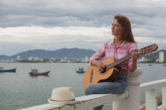 Schönes rothaariges Mädchen mit einer Gitarre Lizenzfreie Stockbilder