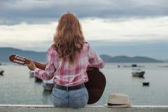 Schönes rothaariges Mädchen mit einer Gitarre Stockfotografie