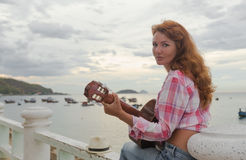Schönes rothaariges Mädchen mit einer Gitarre Stockfoto