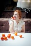 Schönes rothaariges Mädchen mit Tangerinen Lizenzfreie Stockbilder