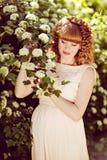 Schönes rothaariges und gelockt-schwangeres Mädchen mit ihren Augen schließen Stockfoto