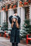 Schönes russisches Mädchen an einem Wolkentag in der Winterkleidung, die Spaß in Tverskaya-Quadrat in der Weihnachtszeit hat stockbild