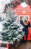 Schönes russisches Mädchen an einem Wolkentag in der Winterkleidung mit Weihnachtsball in den Händen, die Spaß in Tverskaya-Quadr lizenzfreie stockbilder
