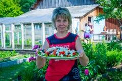 Schönes russisches Mädchen mit einer Platte des köstlichen und gesunden Lebensmittels Stockfotos