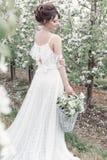 Schönes süßes leichtes glückliches Mädchen in einem beige Boudoirkleid mit Blumen in einer Korbholding, Foto, das im Stil Umb. ve Stockbilder