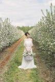 Schönes süßes leichtes glückliches Mädchen in einem beige Boudoirkleid mit Blumen in einer Korbholding, Foto, das im Stil Umb. ve Lizenzfreie Stockbilder