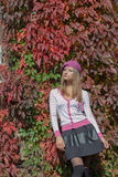 Schönes süßes Mädchen in einem Barett und in einem Rock geht unter der hellen roten Farbe von Blättern am hellen sonnigen Tag des Stockfotografie