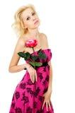 Schönes, süßes Mädchen mit einer Rose in einem Kleid Stockfoto