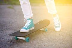 Schönes schönes Mädchen fährt auf Landstraße auf szenischer Straße Longboard Solartonen Ein Nahaufnahmeporträt Stockbilder