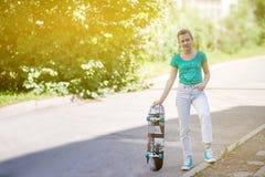 Schönes schönes Mädchen fährt auf Landstraße auf szenischer Straße Longboard Solartonen Ein Nahaufnahmeporträt Lizenzfreie Stockfotografie