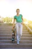 Schönes schönes Mädchen fährt auf Landstraße auf szenischer Straße Longboard Solartonen Ein Nahaufnahmeporträt Lizenzfreie Stockbilder