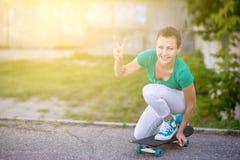 Schönes schönes Mädchen fährt auf Landstraße auf szenischer Straße Longboard Solartonen Ein Nahaufnahmeporträt Lizenzfreies Stockbild