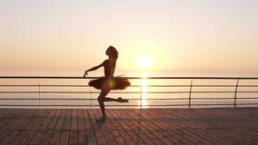 Schönes Schattenbild der Ballerina im Ballettballettröckchen und des Punktes auf Damm über Ozean oder Meer bei Sonnenaufgang Jung stock video footage