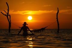Schönes Schattenbild der jungen Frau mit dem Schwingen, das im Meer auf Sonnenuntergang, maledivische romantische Landschaft auf lizenzfreie stockfotos