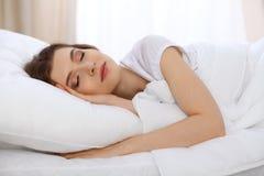 Schönes Schlafenim Bett morgens liegen der jungen Frau und sich entspannen Sonniger Tagesanfänge ist- die Zeit, eine Arbeit anzus lizenzfreie stockfotografie